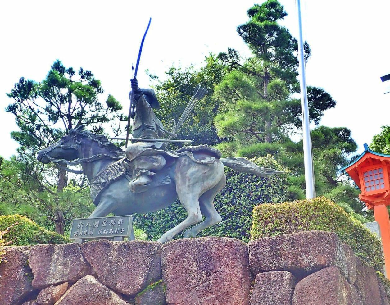 穴八幡宮の鳥居の後ろにある流鏑馬の像